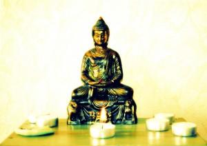 Estatuilla de Buda en color bronce sobre mesa, con velas blancas alrededor.