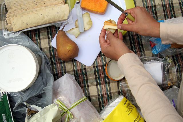 Manos masculinas preparando una merienda sobre un mantel y comida para picnic