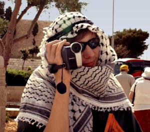 primer plano de hombre sosteniendo una cámara de aficionado cubierto con manto árabe