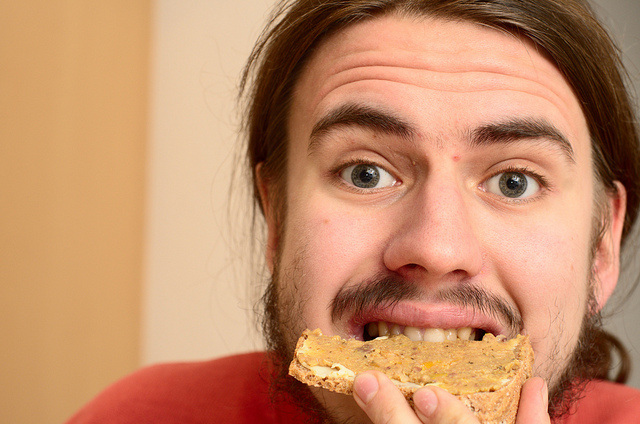 hombre joven mordiendo pedazo de pan
