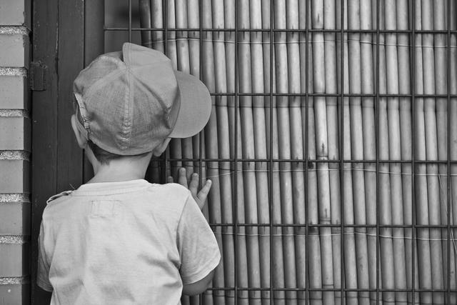 niño con gorra viendo el interior de una habitación a través de una cortina