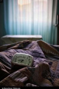 imágen de reloj despertador sobre mantas desordenadas
