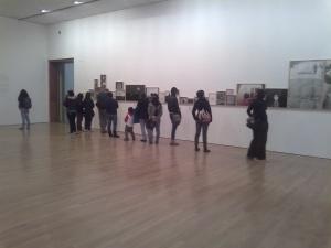 gente viendo fotografías en la sala de un museo
