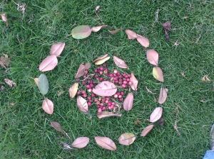 Mandala hecho con hojas secas y frutos rojos sobre el pasto