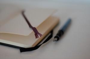 libreta con hojas en blanco y pluma