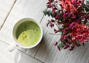 taza de té matcha vista desde arriba junto a flores rojizas sobre mesa de madera pintada de blanco al estilo wash